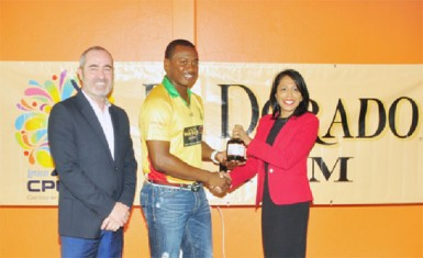 Jamie Stewart (left) watches on as Amazon Warrior's Chris Barnwell receives a bottle of 21 year-old rum from DDL's Marketing Director Sharda Vereen-Chand.