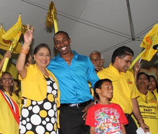 West Indies player Dwayne Bravo with Prime Minister Kamla Persad-Bissessar at the United National Congress' Monday Night Forum in Debe.