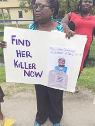Coordinator Roxanne Myers holding a placard