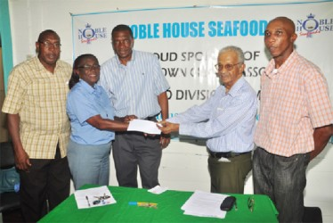 Secretary of the  GCA Deborah McNichol receives the cheque from Noble House Seafoods representative Percy Corlette.