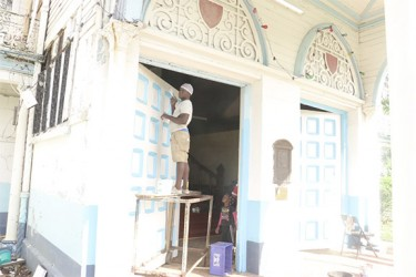 A worker painting the door at the Avenue of Republic entrance to City Hall, which will be used for next week's nomination day activities