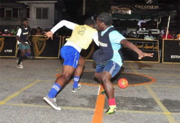 Melanie-B's Akeem Bacchus (left) dribbling past Carlos Kingston (right) in the centre of the tarmac during their team's semi-final encounter