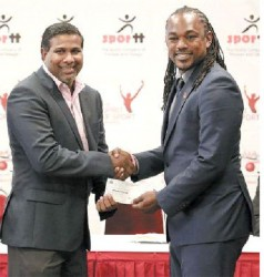 Former WIPA president Dinnanath Ramnarine receives a check valued at TT$15,000 from Minister of Sports, Senator Brent Sancho during the distribution of cheques to local cricket clubs at the VIP Lounge, Hasley Crawford Stadium.
