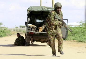 A Kenya Defense Force soldier runs for cover near the perimeter wall where attackers are holding up at a campus in Garissa April 2, 2015. Reuters/Noor Khamis