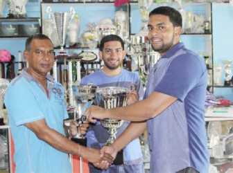 In picture Managing director of Trophy stall Ramesh Sunich presents one of the trophies to be competed for at the Guyana Cup Fever horse race meet to organiser Nazrudeen 'Jumbo Jet' Mohammed Jr., while overseas-based Guyanese Ricky Azrula holds one of the trophy at centre. The Trophy Stall apart from providing all the trophies for the Guyana Cup Fever horse race meet will also be providing the trophies for the top jockey, runner up, stable and trainer.