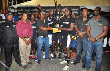 Beterverwagting A's captain Delroy Deen collects the championship trophy from Banks DIH Limited East Coast Area Manager Clive Pellew while members of the winning team, Banks DIH and Petra Organisation officials look on. (Orlando Charles photo)