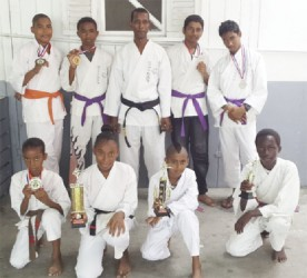 Members of the successful Black Cobra Karate Club of Parfaite Harmonie alongside sensei Lloyd Ramnarine (centre) displaying their respective medals and trophies earned during the Guyana Classic of Classic Martial Arts Tourney