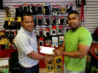 Organizing Secretary of the GABBFF, Videsh Sookram (right) receiving the sponsorship cheque from Fitness Express' manager Ian Rogers yesterday at the company's 47 John and Sheriff Streets location.