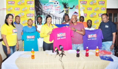 Sherwin `Lalai' Grimes of Globe Yard receiving his team's uniform from Busta Brand Manager Christine Kellawan while other members of the participating teams, Petra Organization Co-Director Troy Mendonca (2nd from left) and Managing Director of Guyana Beverage Company Robert Selman (right) look on.