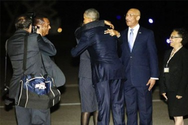 U.S. President Barack Obama (C, back to camera) gets a hug from Jamaica's Prime Minister Portia Simpson Miller as he arrives aboard Air Force One at Norman Manley International Airport in Kingston, Jamaica April 8, 2015.  Reuters/Jonathan Ernst