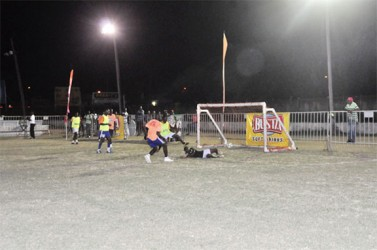 Rafael Edwards (orange) of Tucville in the process of scoring his side's third goal, equalizing the matchup against Leopold Street during the second match of the night.