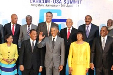 Prime Minister Kamla Persad-Bissessar, left front row, is all smiles as she looks at a waving United States President Barack Obama prior to a meeting with leaders of CARICOM countries at the Mona Campus of the University of the West Indies, Kingston, Jamaica, yesteday afternoon. The Prime Minister of Jamaica, Portia Simpson-Miller, on the right of the President, welcomed the US President to her country. Perry Christie, Prime Minister of the Bahamas, and Chairman, of CARICOM, next to the President, in welcoming Obama, raised issues which CARICOM needed to be addressed. (Trinidad Express photo)