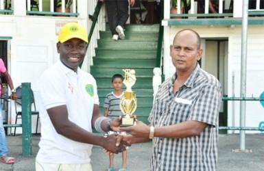 Essequibo MVP Keanu Harry receives his trophy from GCB Chairman of Junior Selectors Nazimul Drepaul.