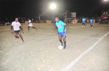 Calvin Shepherd of Holmes Street Tiger Bay on the attack down the left flank while being pursued by Shaka Jones of Albouystown during the two teams' matchup.
