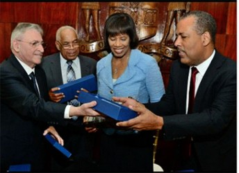 President of Terminal Link and Executive Officer of CMA CGM Group, Farid Salem (left) presents gifts to Minister of Transport Dr Omar Davies (second left), Prime Minister Portia Simpson Miller, and President/CEO of the Port Authority of Jamaica Professor Gordon Shirley (right) at the signing ceremony for the 30-year concession agreement for Kingston Container Terminal, at the Office of the Prime Minister, Kingston on April 7, 2015.