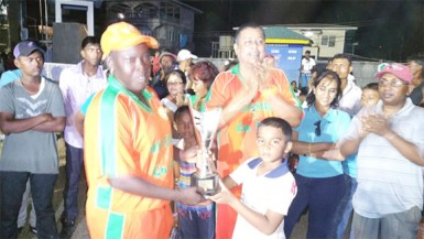 Young Richie Deonarain hands over the trophy to Erva Giddings of the Karibee Girls following their team's defeat of Trophy Stall Angels last Sunday at Crabwood Creek.