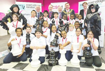 Students, teachers and elected political officials pose for a photograph beside enlarged chess pieces and chess board in 2013 in Newham, London. Chess was delivered to 64 schools in Newham and 20,000 children, who learnt to play the world's most enduring game.
