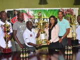 Manager of Slingerz FC Colin Aaron (left) collecting the championship trophy from ANSA McAl PRO Darshanie Yussuf while other members of the launch party look on