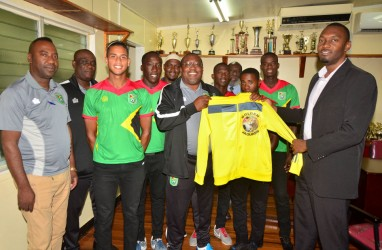 Head Coach Jamaal Shabazz presents Director of Sports Christopher Jones with memorabilia during the National U-23 team's courtesy call yesterday