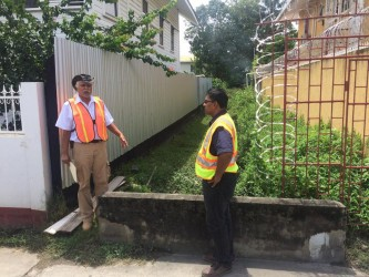 Walter Willis (left) and GAICO Managing Director, Komal Singh standing at one of the alleys on New Market Street between Camp and Thomas streets.