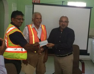 Suresh Narine (right) handing the cheque to GAICO managing director, Komal Singh