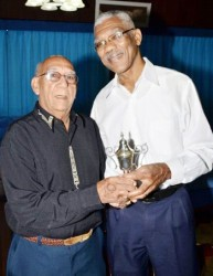 Pat Holder (left), former motorcycle racer, and chief race starter presenting President David Granger with a trophy, which he won when he was just 14 years old (GINA photo)