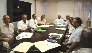 This GINA photo shows the team meeting with Agriculture Minister Noel Holder (at head of table)