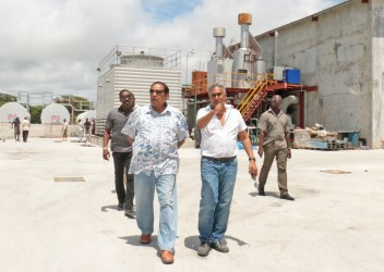 Prime Minister Moses Nagamootoo (left) being shown around the Giftland Mall site by its President Roy Beepat. Behind them is the mall's power plant.