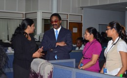 Minister of Legal Affairs and Attorney General Basil Williams (second from left) pays attention as he is informed by Registrar Azeena Baksh about the responsibilities and roles of the staff of the Deeds Registry