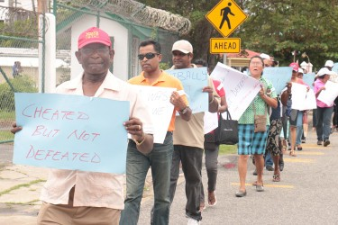 Former Local Government Minister Ganga Persaud bearing a placard outside GECOM, last month.