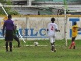 New Campbellville Secondary's Trevon Pluck (yellow) converting his penalty attempt into the lower left hand corner during his team's lopsided win over Sophia Training Centre at the Tucville Community ground
