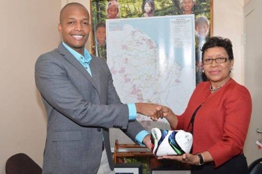 GFF Normalization Committee Chairman ClintonUrling (left) hands overa ball to Minister within the Ministryof Indigenous Affairs Valerie Lowe-Garrido during a brief handing over ceremony. (Orlando Charles photo)