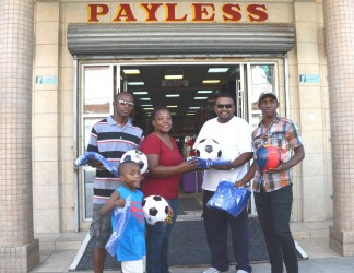 Secretary of the Order and Discipline Football Club Nicola Lambert receives the donation of equipment from Rajan Tiwari of Payless Variety Store, (second right) as coach Mark DeBarros (left) and club captain, Ken Wilson look on.