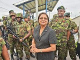 Heavy guard: Prime Minister Kamla Persad-Bissessar is surrounded by defence force troops during a visit on Saturday to Crown Trace, Enterprise, where an apparent gang war has erupted in the past few weeks.