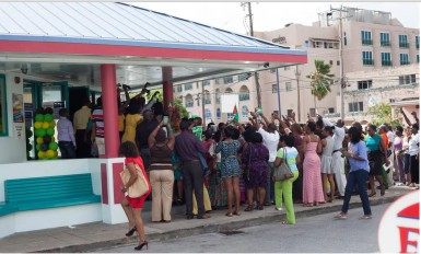 Guyanese gathered outside Bubba's Sports Bar in Hastings, Christ Church, Barbados try to get a glimpse and take a photo of the president.