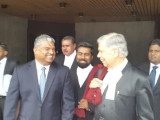 Anand Ramlogan (left) leaving the Hall of Justice with his lawyers.