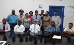 Minister Ronald Bulkan (seated at centre) with senior management and staff of the customer services team. (GWI photo)