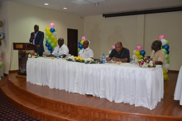 Minister of State Joseph Harmon speaking at the luncheon. Minister of Governance, Raphael Trotman is second from right.