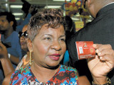 Cheryl Worrell displays her biometric Smart Card for the media during the launch of the Government's latest social initiative at Xtra Foods Supermarket in Grand Bazaar, Valsayn.