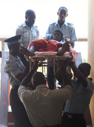 Warren McKenzie, who is accused of robbing land court judge Nicole Pierre and her husband, Mohamed Chand, was taken to court on a stretcher yesterday to be charged. (Photo by Keno George)