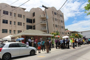 GRA employees outside the agency's Camp Street headquarters after a tremor on July 16th. GRA Board Chairman Rawle Lucas confirmed to Stabroek News that cracks developed in the building after this event. (Stabroek News file photo)