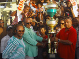Handlers of Just Call Me Boss accepting the large winner's trophy compliments of the Trophy Stall of Bourda Market. (Orlando Charles photo)