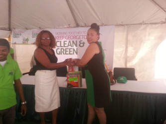 Deputy Mayor Patricia Chase-Green (at right) receives a donation of garbage bags from a public-spirited citizen
