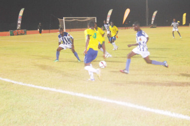 Pele's Travis Grant (centre) on the attack on the left side of the wing while being pursued by several GFC's players during their GFF Stag Beer Elite League tournament opener at the Leonora Sports Facility. (Orlando Charles photo)