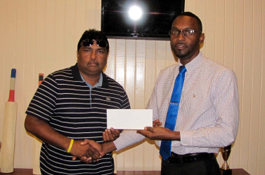 Director of Sports Chris Jones hands over the $250, 000 sponsorship check to BCB President Anil Beharry.