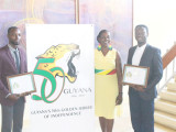 Golden Jubilee logo: The winners of Guyana's 50th Independence Anniversary logo competition, Christopher Taylor (right) and Compton Babb (left), pose with Junior Education Minister Nicolette Henry in front of their winning design. (Photo by Keno George)