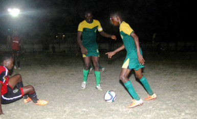 Jamal Codrington (left) of Alpha United lying on the ground after getting disposed of possession by his GDF marker during their team's matchup in the GFF Stag Beer Elite League