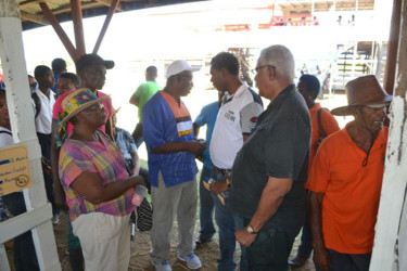 Agriculture Minister Noel Holder (second from right) interfacing with farmers at the exhibition