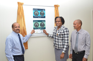 Governor of the BoG Gobind Ganga (left) and Minister Annette Ferguson (centre) unveiling the two commemorative stamps for the bank's 50th anniversary as Post Master General Abdul Hassan looks on.