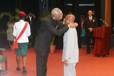 In this Keno George photo, President David Granger presents the national award. The ceremony was held at the National Cultural Centre.
